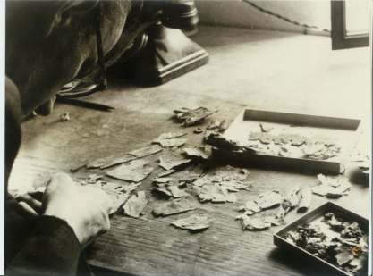 On the 'Scrollery' workbench, Joseph Milik with scroll fragments newly purchased on their receipt from the finders, c.1956.